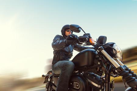 Een jonge man rijdt op een bijl op een weg in motion blur Stockfoto