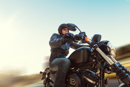 A young man riding a chopper on a road in blur motion