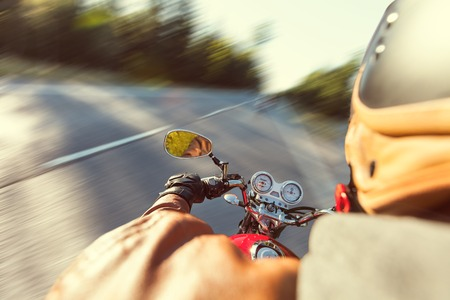 shot from behind: Biker riding motorcycle  on road in morning sunny day in blur motion capture. Shot from behind Stock Photo
