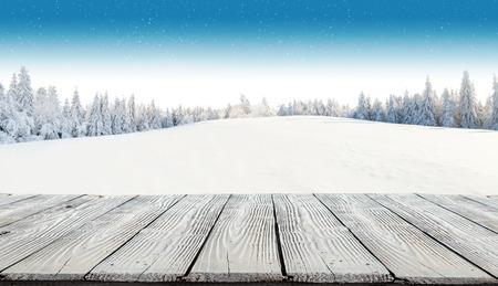 Winter-Hintergrund mit Haufen von Schnee und Unschärfe Landschaft. Leere Holzbohlen auf Vordergrund. Copyspace für Text