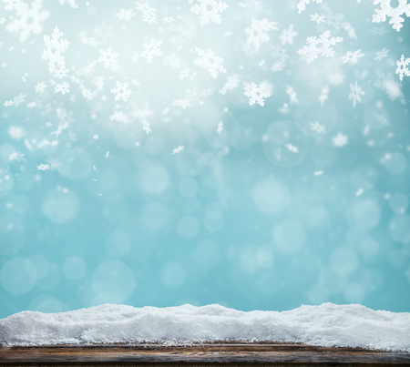 Winter background with pile of snow and blur abstract lights. Empty wooden planks on foreground. Copyspace for text