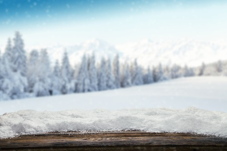 Winter background with pile of snow and blur landscape. Empty wooden planks on foreground. Copyspace for text Stockfoto