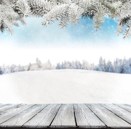 montañas nevadas: Fondo del invierno con pila de nieve y el paisaje borroso. tablones de madera vacías en primer plano. Copyspace para el texto