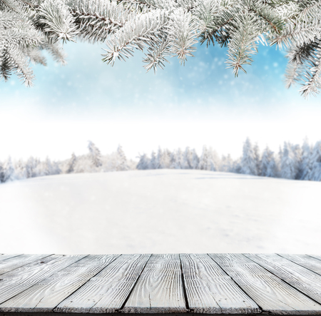 forest wood: Winter background with pile of snow and blur landscape. Empty wooden planks on foreground. Copyspace for text Stock Photo