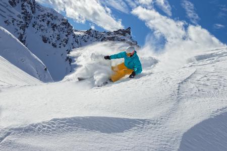 downhill: Man skier running downhill on sunny Alps slope Stock Photo