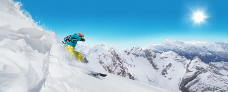 fun in the sun: Man skier running downhill on sunny Alps slope Stock Photo