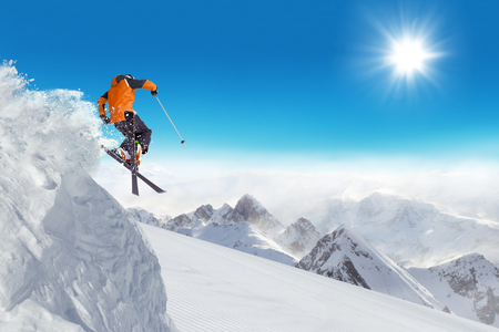 skier jumping: Jumping skier at jump with alpine high mountains