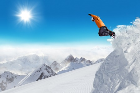 jumps: Jumping snowboarder at jump with alpine high mountains Stock Photo