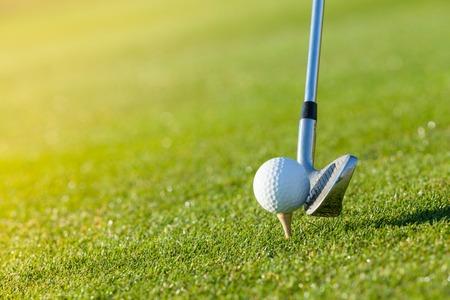 Golf club en bal in het gras, lage diepte van de focus