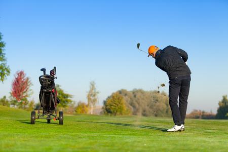 golf ball on tee: Man playing golf on green golf course. Hitting golf ball