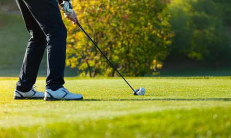 sky and grass: Close-up of man playing golf on green golf course. Hitting golf ball