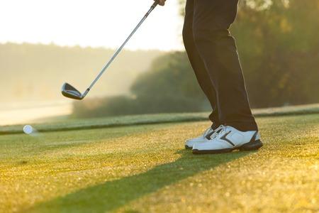 columpio: Primer plano de hombre jugando al golf en el verde campo de golf. Golpear la pelota de golf
