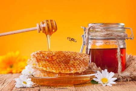 frasco: Tarro de miel fresca con cazo, que se presentan en tablas de madera Foto de archivo