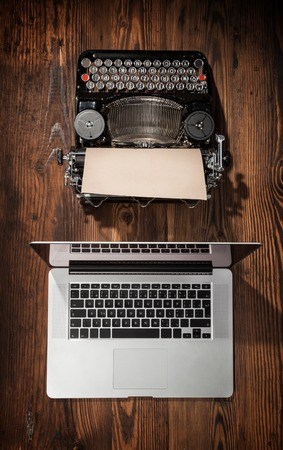 progress: Old typewriter with laptop placed on wooden table. Concept of technology progress
