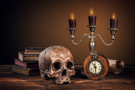 verdict: Still life art photography on human skull skeleton with blank scroll and books. Concept of judge verdict Stock Photo
