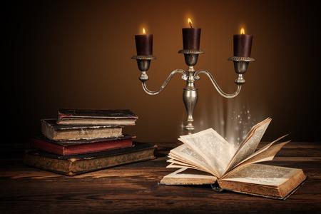 libros antiguos: libros antiguos viejos con velas en candelabro. estilo retro de edad