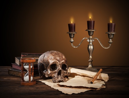 manuscript: Still life art photography on human skull skeleton with blank scroll and books. Concept of judge verdict Stock Photo