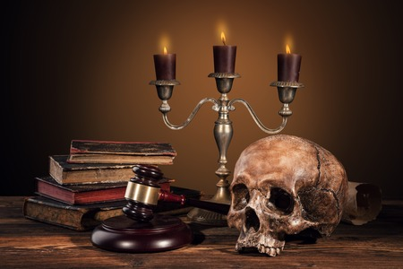 verdicts: Still life art photography on human skull skeleton with blank scroll and books. Concept of judge verdict Stock Photo