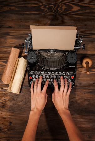the typewriter: Mujer escribiendo en una m�quina de escribir, colocado sobre la mesa de madera Foto de archivo