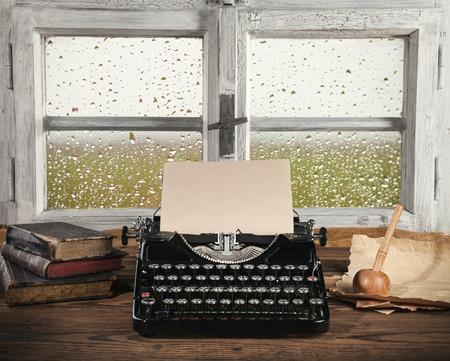 汚れた木製窓とアンティークのタイプライター。ビンテージの静物