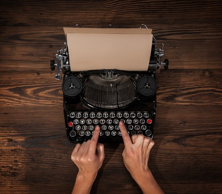 detective agency: Woman typing on an old typewriter, placed on wooden table