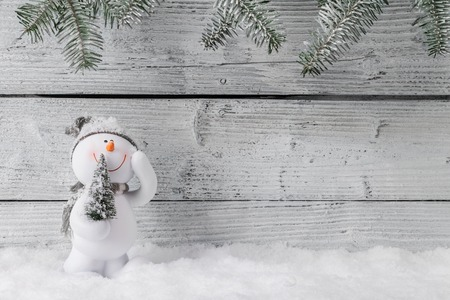 Christmas still life decoration with snowman on wooden background. Imagens