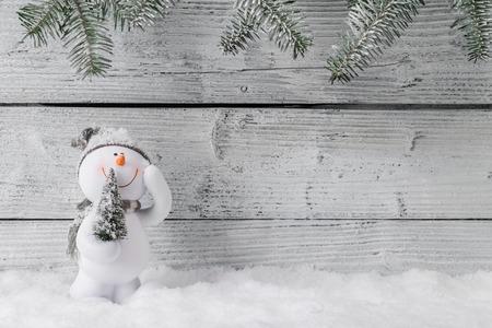 Christmas still life decoration with snowman on wooden background. Standard-Bild