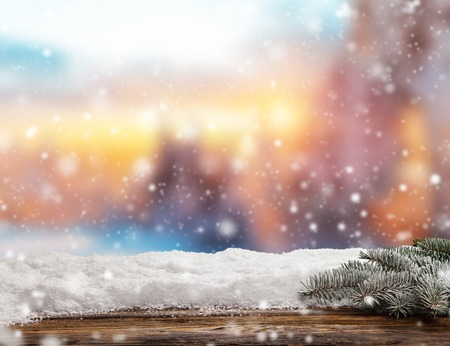 Winter background with pile of snow and blur evening landscape. Empty wooden planks on foreground. Copyspace for text Imagens