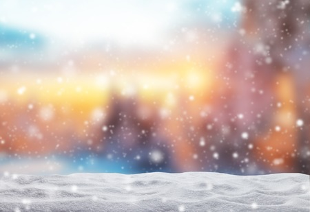 Winter background with pile of snow and blur evening landscape. Copyspace for text