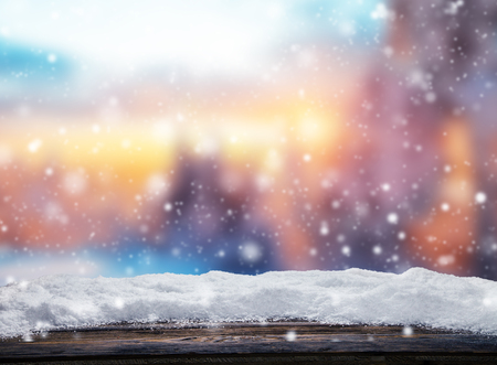 Winter background with pile of snow and blur evening landscape. Empty wooden planks on foreground. Copyspace for text Standard-Bild