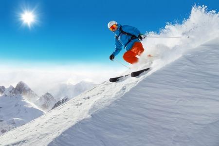 Man skier running downhill on sunny Alps slope 스톡 콘텐츠
