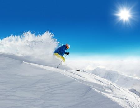 SKI: Man skier running downhill on sunny Alps slope Stock Photo