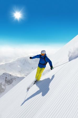 verticales: Hombre esquiador corriendo cuesta abajo en la pendiente soleada Alpes Foto de archivo
