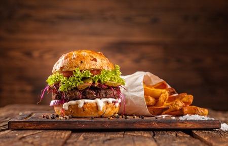 papas fritas: Deliciosa hamburguesa servida en tablones de madera