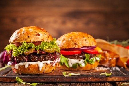 木の板においしいハンバーガーを提供しています