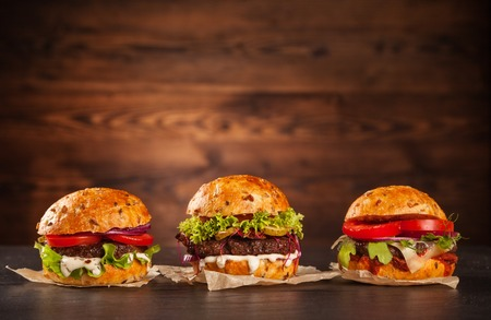 Delicious hamburgers served on wooden planks Imagens - 47420814