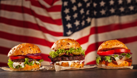 Delicious hamburgers served on wooden planks. Flag of USA as background