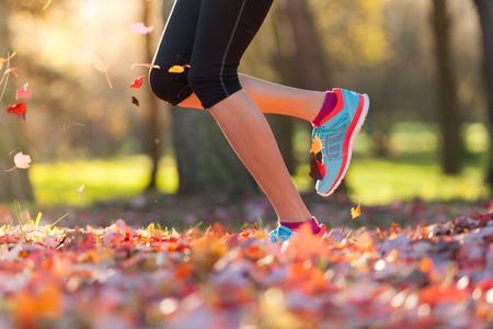 exteriores: Cerca de los pies de running mujer en hojas de otoño. Ejercicio de la aptitud, la baja profundidad de foco