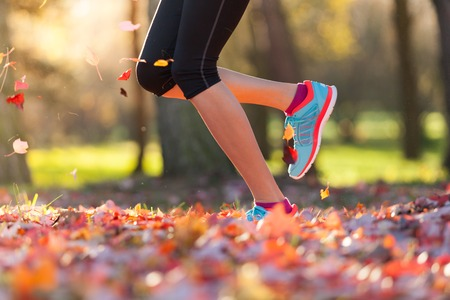 young woman legs up: Close up of feet of female runner running in autumn leaves. Fitness exercise, low depth of focus Stock Photo