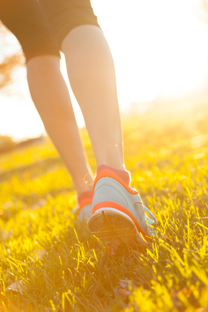 Close up of feet of female runner running in grass. Fitness exercise, low depth of focus Stock Photo