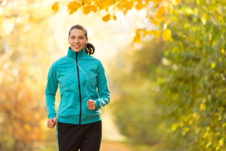fitness training: Female fitness model training outside and listening to music. Sport and healthy lifestyle Stock Photo
