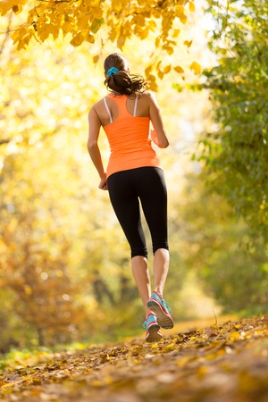 shot from behind: Female fitness model training outside and running. Sport and healthy lifestyle. Shot from behind Stock Photo