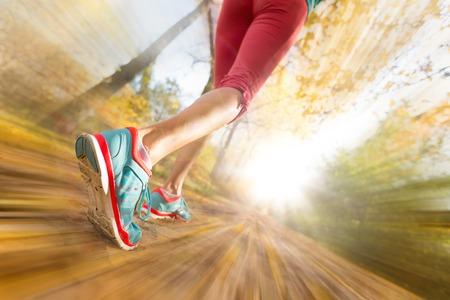 Primer plano de los pies de atleta femenina que se ejecutan en hojas de otoño. Ejercicio de la aptitud. Desenfoque de movimiento