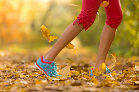 trainers: Close up of feet of female runner running in autumn leaves. Fitness exercise, low depth of focus Stock Photo