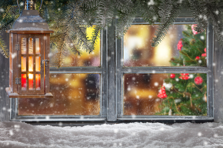Atmospheric Christmas window sill decoration with home cozy interior. Christmas tree on background Imagens