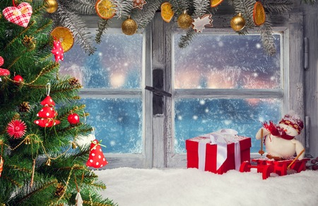 Atmospheric Christmas window sill decoration with beautiful sunset view.Christmas tree on foreground Archivio Fotografico