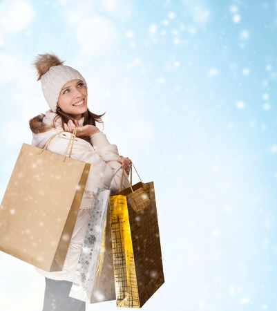 lovely woman with shopping bags on abstract winter background Stock Photo