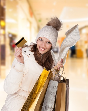 credit card purchase: Happy brunette girl in winter dress posing in shopping mall, holding credit card