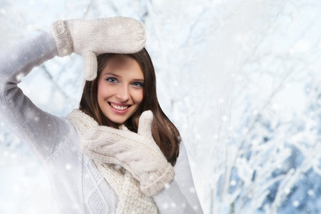 frozen winter: Beautiful winter portrait of young brunette woman showing photo frame guesture in the winter snowy scenery Stock Photo