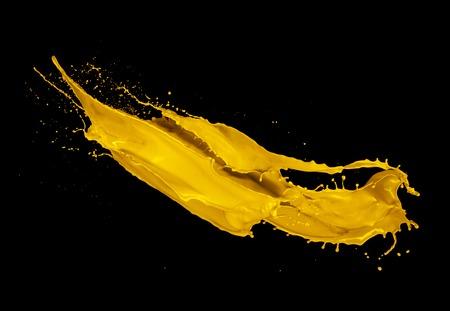 amarillo y negro: Amarillo chapoteo de la pintura aislado en el fondo negro Foto de archivo